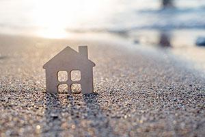 Haussymbol im Sand am Meer