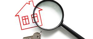 Hauszeichnung unter einer Lupe und ein daneben liegender Schlüssel