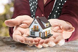 Hausmodell in den Händen als Geschenk