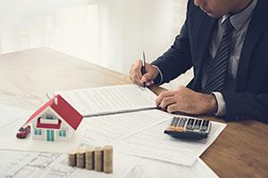 Makler mit Unterlagen, Taschenrechner und Hausmodell