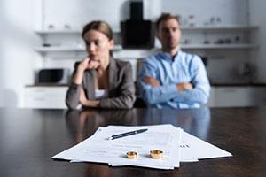 Ehepaar sitzt am Tisch mit Scheidungsunterlagen