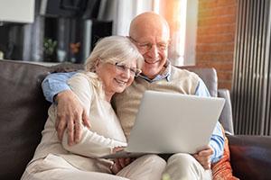 Älteres Paar auf einem Sofa, sucht etwas im Internet
