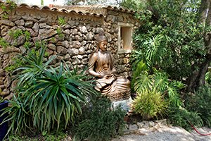 Buddha an zugewachsener Mauer