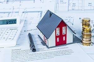 Miniatur Einfamilienhaus mit Taschenrechner und Finanzierungsunterlagen