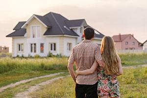 Paar blickt auf gekauftes Einfamilienhaus
