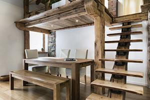 Rustikaler Wohnbereich mit Holztreppe