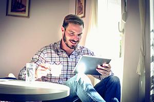 Mann am Tisch mit Tablet und Kaffee