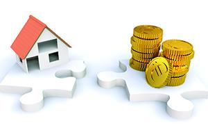 Miniatur Haus und Geld auf zwei Puzzlestücken