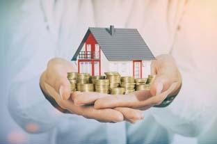 Miniaturhaus und Geld in der Hand eines Maklers