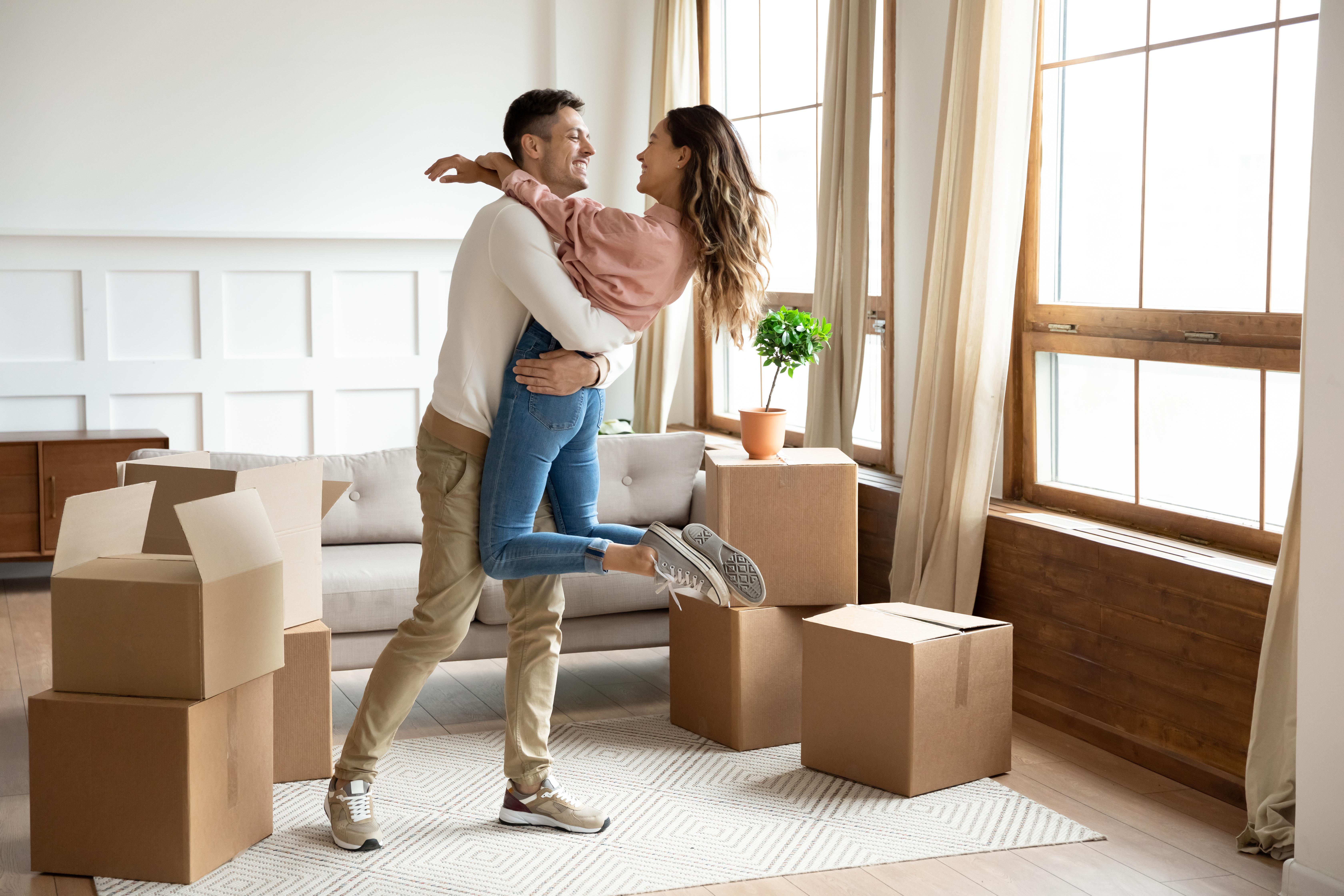 Paar umarmt sich zwischen Kartons