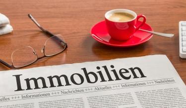 Zeitung zu Immobilien mit Kaffee und Brille auf einem Tisch