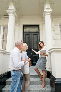 Makler berät Paar zur Immobilie
