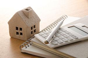 Miniaturhaus und Taschenrechner zur Wertermittlung