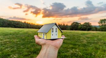 Hand hält kleines Haus