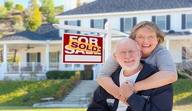 Zwei Senioren vor einem verkauften Haus