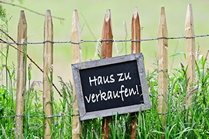 """Schild am Gartenzaun """"Haus zu verkaufen"""""""