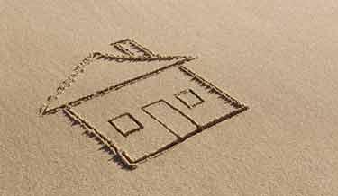 In Sand gezeichnetes Einfamilienhaus